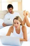 Mulher carismática que usa um portátil que encontra-se na cama imagem de stock