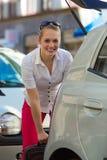 A mulher carrega a mala de viagem na bota ou no tronco do carro Fotografia de Stock Royalty Free