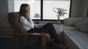 Mulher casada que senta-se perto da janela que fala no telefone vídeos de arquivo