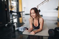 A mulher caucasiano atrativa no sportswear est? usando um telefone esperto e est? sorrindo ao colocar na esteira da ioga imagem de stock