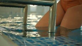 Mulher caucasiano atrativa nova na saída alaranjada do roupa de banho a piscina pelo tiro do movimento lento da escada do metal filme