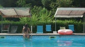 Mulher caucasiano atrativa nova na saída do biquini a piscina pelo tiro do movimento lento da escada do metal video estoque