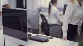 A mulher caucasiano atrativa trabalha no computador no escritório filme