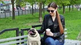 Mulher caucasiano bonita com o cão engraçado do pug que senta-se no banco e no café bebendo filme