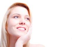 Mulher caucasiano bonita que acaricia sua cara e que sorri para um espaço da cópia Fotografia de Stock