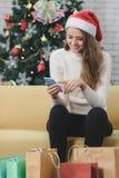 Mulher caucasiano bonita nova no chapéu vermelho que senta-se no sofá no franco foto de stock royalty free