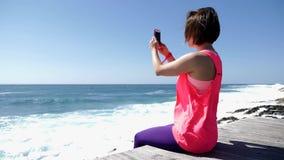 Mulher caucasiano bonita nova que senta-se no telefone da terra arrendada da praia rochosa e que toma fotos Movimento lento video estoque