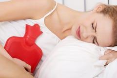 Mulher caucasiano bonita que encontra-se com o saco de água quente Foto de Stock