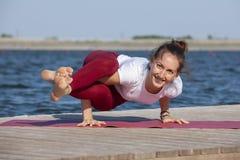 Mulher caucasiano bonita que exercita a ioga na natureza ao lado de um lago fotos de stock royalty free