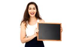 Mulher caucasiano bonita que guarda o quadro-negro vazio sobre o fundo branco Imagem de Stock Royalty Free