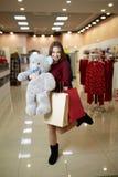 A mulher caucasiano bonito nova atrativa abraça o urso de peluche do luxuoso com os sacos de compras na parte dianteira da loja d Foto de Stock Royalty Free