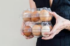 Mulher caucasiano com a camisa preta que mantém duas caixas de ovo plásticas completas de ovos da galinha fotos de stock royalty free