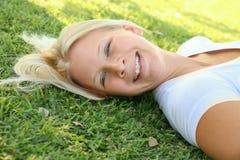 A mulher caucasiano de riso feliz relaxa na grama fotos de stock