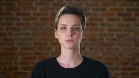Mulher caucasiano de vista séria da câmera com cabelo curto e a cara concentrada, estando ao lado do frio da parede de tijolo video estoque