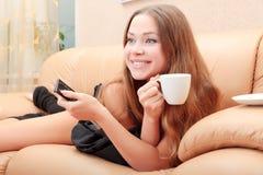Mulher caucasiano deleitada que presta atenção a uma mostra de tevê Fotografia de Stock
