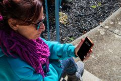 Mulher caucasiano envelhecida média do nascido no Baby Boom que olha de vista seu telefone com raiva A tela do telefone celular d imagens de stock royalty free