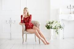 Mulher caucasiano feliz em um bodysuit vermelho do laço e sitted com os pés descalços em uma cadeira com olhar frontal em uma sal fotos de stock royalty free
