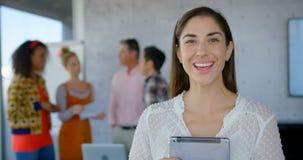 Mulher caucasiano feliz que guarda uma tabuleta digital e que olha a câmera 4k video estoque