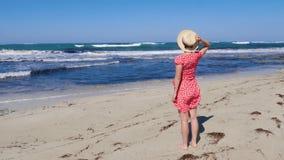 A mulher caucasiano guarda seu chapéu em um vestido vermelho que olha a posição tormentoso do mar e do horizonte na praia da arei filme