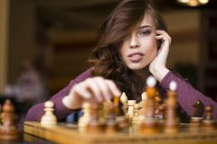 Mulher caucasiano inteligente nova que joga a xadrez em casa que veste a roupa ocasional esperta fotos de stock