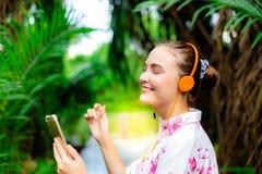 A mulher caucasiano lindo é a música agradável de escuta que pode curar d fotografia de stock