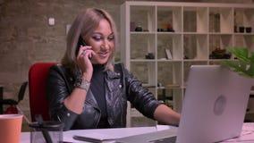 A mulher caucasiano loura bonita está falando sobre o smartphone e está sentando-se calmamente no desktop, olhando seus portátil  filme