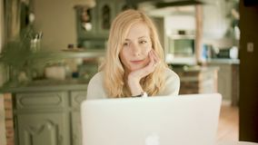 Mulher caucasiano loura em casa que olha seu sorriso do portátil video estoque