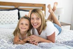 Mulher caucasiano loura nova que encontra-se na cama junto com seus 7 anos doces e adoráveis novos da filha idosa em casa b relax Imagens de Stock