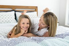 Mulher caucasiano loura nova que encontra-se na cama junto com seus 7 anos doces e adoráveis novos da filha idosa em casa b relax Imagem de Stock