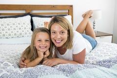 Mulher caucasiano loura nova que encontra-se na cama junto com seus 7 anos doces e adoráveis novos da filha idosa em casa b relax Fotografia de Stock Royalty Free