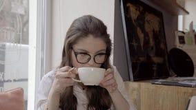 Mulher caucasiano moreno no funcionamento de vidros em um café com portátil, 4K video estoque