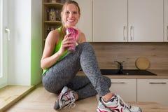 Mulher caucasiano na agitação bebendo da proteína do terno de gym na cozinha Imagem de Stock Royalty Free
