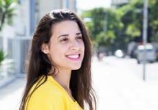 Mulher caucasiano na camisa amarela na cidade que olha lateralmente fotografia de stock royalty free