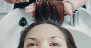 A mulher caucasiano no salão de beleza tem um tratamento do cabelo com o armário profissional do cabelo filme