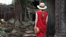 A mulher caucasiano no vestido vermelho está andando entre ruínas de Ta Prohm filme