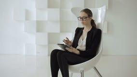 Mulher caucasiano no vestuário formal à moda preto com a tabuleta nas mãos filme