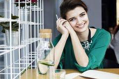 A mulher caucasiano nova bonita em torno do sorriso trinta feliz de assento no café, comendo o café da manhã, bebe o waterÑŽ puro Foto de Stock