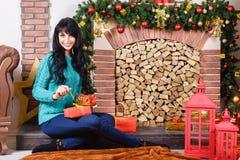 Mulher caucasiano nova bonita que senta-se perto de um firepl decorativo imagens de stock