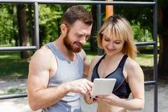 Mulher caucasiano nova e um homem farpado que consulta o Internet sobre Fotos de Stock