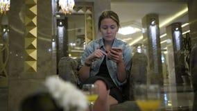 A mulher caucasiano nova em um revestimento das calças de brim bebe o suco de um vidro e usa um smartphone, escreve mensagens no  video estoque