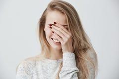 A mulher caucasiano nova emocional bonita com o cabelo longo louro, fechando-se eyes com mão ao rir para fora ruidosamente imagem de stock royalty free