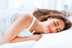 Mulher caucasiano nova feliz que sorri e que dorme na cama com abrandamento e mente tranquilo e calma no fundo branco Imagens de Stock Royalty Free