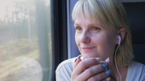 A mulher caucasiano nova monta em um compartimento do trem, guarda um smartphone em sua mão, escuta a música em fones de ouvido filme