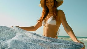 Mulher caucasiano nova no biquini e no chapéu que jogam com o lenço na praia na luz do sol vídeos de arquivo