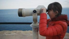 Mulher caucasiano nova no revestimento vermelho da bolha que olha a costa de mar no telescópio do elevado alto vídeos de arquivo