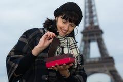 Mulher caucasiano nova que abre uma caixa de presente com presente Imagem de Stock