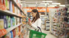 Mulher caucasiano nova que compra produtos éticos do creme do cuidado do corpo no supermercado video estoque