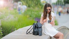 A mulher caucasiano nova que envia a mensagem e escuta música exterior na cidade europeia Menina bonita nos óculos de sol que sen filme