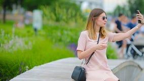A mulher caucasiano nova que envia a mensagem e escuta música exterior na cidade europeia Menina bonita nos óculos de sol que sen video estoque