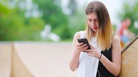 A mulher caucasiano nova que envia a mensagem e escuta música exterior na cidade europeia Menina bonita nos óculos de sol que sen vídeos de arquivo